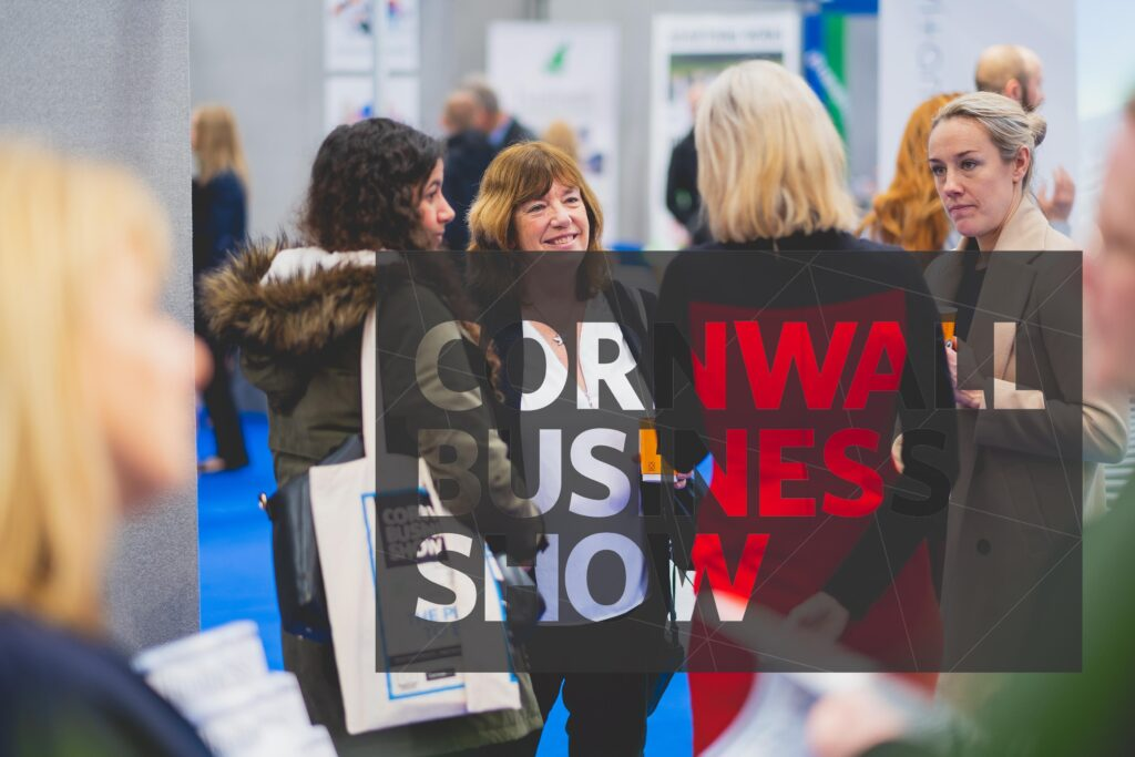 A happy group of visitors talk to a business exhibitor at Cornwall Business Show